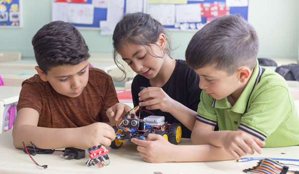 elementary students working together on a small robot at a classroom table