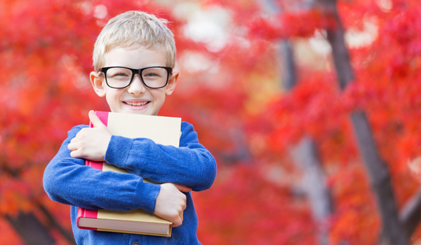 elementary age kid with glasses hugging a book outdoors in the Autumn