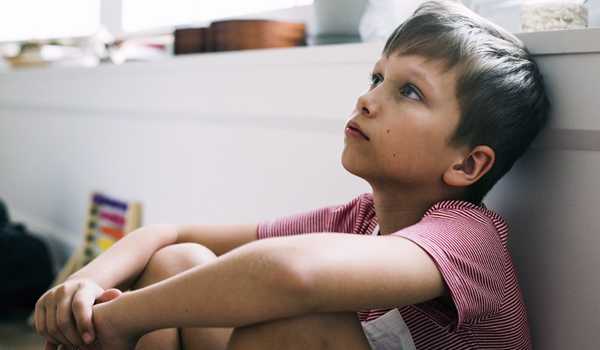 child sitting on the floor with his back against the wall and his elbows on his knees