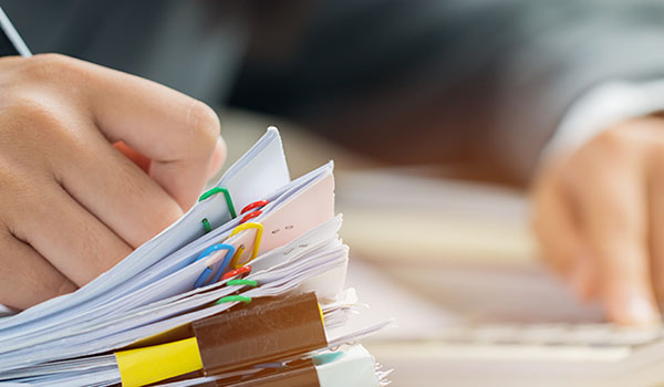 closeup of hands holding a writting utensil on top of a stack of clipped papers