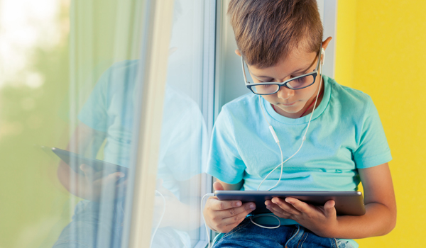 elementary age boy sitting by a window with an tablet, headphones, and eyeglasses